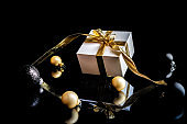 Gift boxes background. White gift box with golden ribbon, New Year balls and winter tree in Christmas composition on black background for greeting card. Christmas, winter, new year concept.