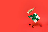 Christmas ornaments. Golden winter tree, white gift box with green ribbon falling with balls and sparkling lights in xmas decoration on reddish background for greeting card. Copy space for your text.