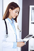 Doctor woman filling up medical form while standing near window in clinic. Physician at work. Medicine and health care concept