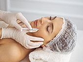 Beautician doing beauty procedure with syringe to face of young brunette woman. Cosmetic medicine and surgery, beauty injections