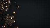 Winter banner. White gift with golden bow, gold balls and sparkling lights garland in xmas decoration on dark background for greeting card. Flat lay, top view, copy space.