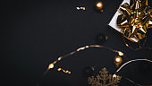 Xmas wreath. White gift with golden bow, gold balls and sparkling lights garland in Christmas decoration on dark background for greeting card. Copy space. Winter holidays, New Year.
