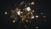 Winter sale. White gift with golden bow, gold balls and sparkling lights garland in xmas decoration on dark background for greeting card. Xmas backdrop with space for text.