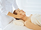 Beautiful woman enjoying facial massage with closed eyes. Spa treatment concept in medicine
