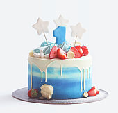 Cake for baby's first birthday with number one figure, berries, marshmallows and star shape decoration on white background.