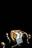 Happy xmas. White gift box with golden ribbon, New Year balls and winter tree in Christmas composition on black background for greeting card. Winter festive composition with copy space.