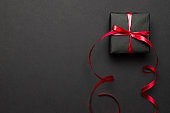 New years background. Christmas gifts with red ribbon on black background. Xmas present. Winter holiday concept. Merry Christmas and Happy Holidays greeting card, frame, banner