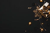 Christmas composition. White gift box with golden ribbon, New Year balls and sparkling lights garland in xmas composition on black background for greeting card. Flat lay, top view, copy space.