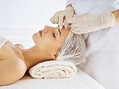Beautiful woman receiving beauty injections with closed eyes. Beautician doctor hands doing beauty procedure to female face with syringe. Cosmetic medicine and surgery concept