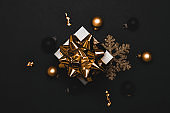 Xmas decoration. White gift with golden bow, gold balls and sparkling lights garland in Christmas decoration on dark background for greeting card. Flat lay, top view, copy space.