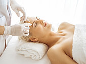Beautician doctor hands doing beauty procedure to female face with syringe. Cosmetic medicine and surgery, beauty injections concept