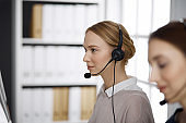 Friendly businesswoman talking by headset in office. Call center and diverse people group in business