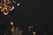 Surprise gift. White gift box with golden ribbon, New Year balls and sparkling lights garland in Christmas composition on black background for greeting card. Flat lay, top view, copy space.