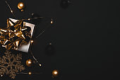Happy new year. White gift with golden bow, gold balls and sparkling lights garland in xmas decoration on dark background for greeting card. Christmas, winter, new year concept.