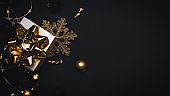 Gift boxes background. White gift box with golden ribbon, New Year balls and sparkling lights garland in Christmas composition on black for greeting card. Winter festive composition with copy space.