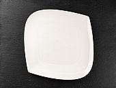 White dish isolated on stone. Round empty plate for dinner. Food background. Restaurant kitchen minimalistic concept.