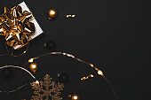Winter background gold. White gift with golden bow, gold balls and sparkling lights garland in xmas decoration on dark background for greeting card. Winter festive composition with copy space.