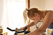 Tired woman after training on exercise bike