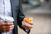 Man hands holding burger and coffee