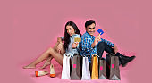 Portrait of cheerful successful happy young lovely couple holding colored shopping bags. Lifestyle Concept.