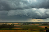 Scenic view of agricultural fields against moody skyy