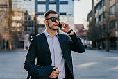 Man in business clothing in street on phone call