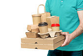 Delivery man holding various take-out food containers, pizza box, coffee cups in holder and paper bag isolated on white.