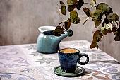 Cup of black coffee on ceramic table. Sun light, shadows