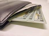 Black wallet full of 100 dollar bill.