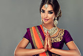 Attractive Indian woman is demonstrating welcome gesture-namaste. Oriental beauty.
