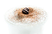 Two roasted coffee beans lie on the milk foam sprinkled with cinnamon powder. Cup of coffee decorated with coffee beans and cinnamon.