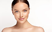 Penetrating look of blue-eyed young woman. Facial treatment, cosmetology, beauty technologies and spa.