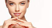 Gorgeous, young woman with clean, fresh skin is touching own face.  Light smile on the perfect face. Cosmetology.