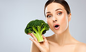 Gorgeous, young woman is holding fresh, green broccoli in the hand. Vegetables, beauty and happiness.