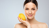 Gorgeous, young woman with clean, fresh skin is holding a big yellow lemon with gentle smile. Light smile on the perfect face. Cosmetology.
