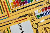 Flatlay of watercolors, brushes, notebooks and other stationery and art supplies on yellow
