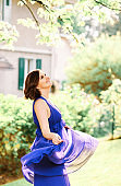 Summer portrait of beautiful charming woman with short haircut wearing purple dress