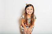 Studio portrait of pretty little girl wearing tiny princess crown, posing on white backgound