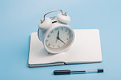 Notebook alarm clock pen on blue background
