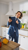 Happy Young Man with Long Hair Using Smartphone in a Kitchen while Wearing Blue Business Suit. He is Cheching Social Meadia and News Feed on His Mobile. Vertical Shot of a Cozy Home.