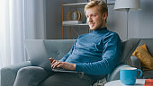 Portrait of Handsome Blonde Young Man Working on a Laptop Computer, While Sitting on a Chair in His Cozy Living Room. Creative Freelancer Relaxes at Home, Surfs Internet, Uses Social Media and Relaxes