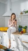 Beautiful Young Female in Striped Jumper and White Pants is Sitting on a Kitchen Furniture and Using Her Smartphone a Modern Sunny Kitchen. She is Happy and Excited while Browsing Social Media.