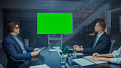 Late at Night In Corporate Meeting Room: Board of Directors, Executives and Businesspeople Sitting at Negotiations Table, Talking and Using Green Mock-up Screen Wall TV for Video Conference Call