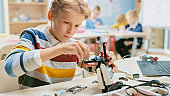 Schoolboy Builds / Constructs Small Robot and Uses Laptop to Program Software for Robotics Engineering Class. Elementary School Science Classroom with Gifted Brilliant Children Working with Technology