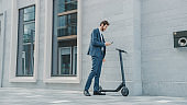 Businessman in a Suit is Activating an Electric Scooter with a Smartphone. He's Scaning the QR Code. Modern Entrepreneur Uses Contemporary Ecological Transport to Go on an Office Meeting.