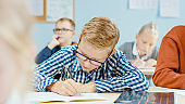 In Elementary School Class: Portrait of a Brilliant Caucasian Boy Wearing Glasses Writes in the Exercise Notebook. Diverse Group of Bright Children Learning Science and Creative Thinking