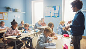 In Elementary School Class: Enthusiastic Teacher walks between Rows of Bright Diverse Children, Dictates Lesson. Group of Smart Multiethnic Kids Writing in Exercise Notebooks.