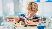 Elementary School Science or Chemistry Classroom: Smart Little Boy wearing Safety Glasses Mixes Chemicals in Beakers