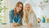 Beautiful Joyful Granddaughter in Jeans Shirt and Happy Senior Grandmother are Posing Together in a Sunny Modern Home Kitchen with Healthy Lifestyle Vibes. Family Set, Smile and Laugh.