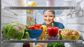 Beautiful Young Woman Looks inside the Fridge and Takes out Vegetables. Woman Preparing Healthy Meal Using Groceries. Point of View POV from Inside of the Kitchen Refrigerator full of Healthy Food